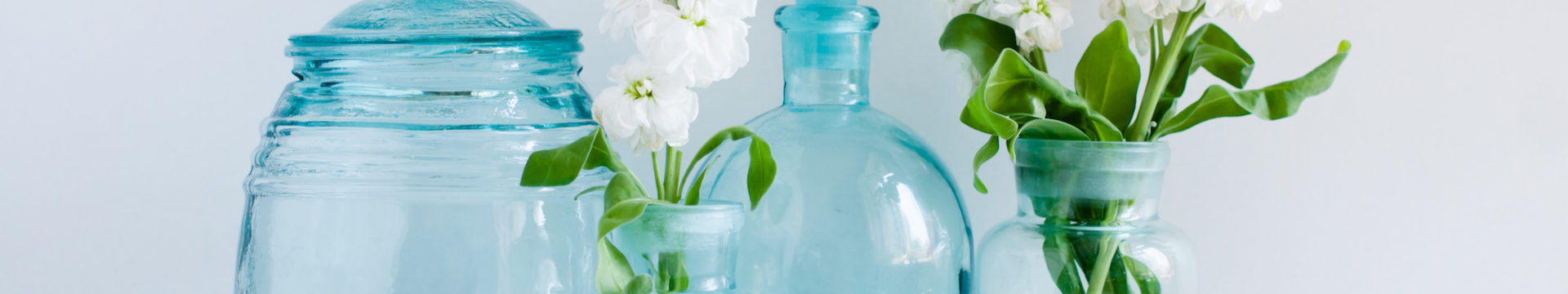 vintage vases with white florals on a rustic shelf