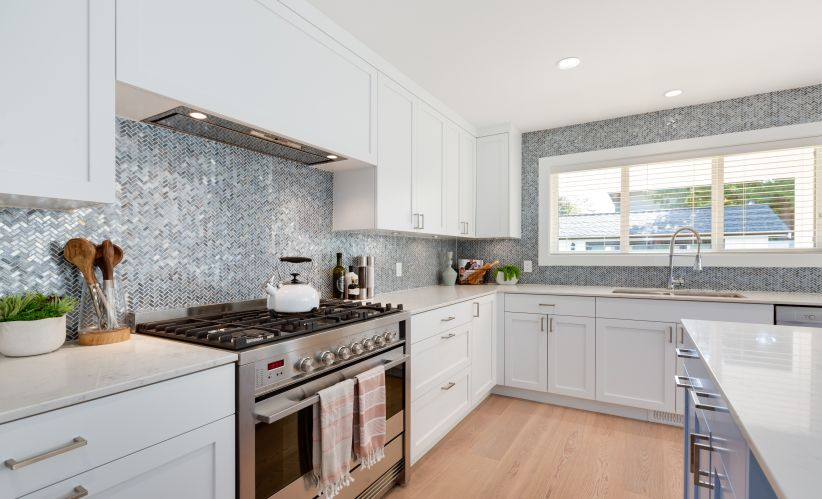 large kitchen with quartz countertops, large island, herringbone pattern backsplash