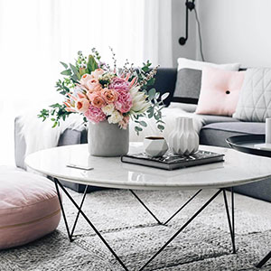 white marble coffee table with pink floral arrangement