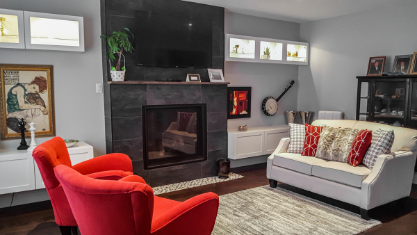 transitional family room with fireplace and red accent chairs, vintage art and wall hung banjo