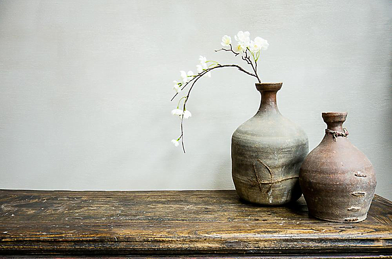 orchid and imperfect japanese vases on rustic distressed table
